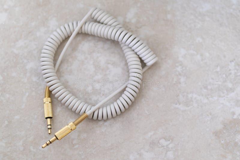 Weißes Audiokabel mit Goldmetall auf einem Marmorhintergrund stockfotografie