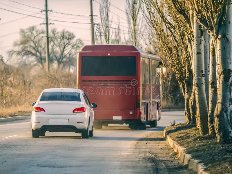 Weißes Auto und roter Bus auf der Straße stockfoto