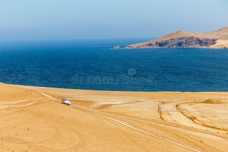 Weißes Autofahren durch Paracas-Wüste in Richtung zum blauen Wasser stockbild