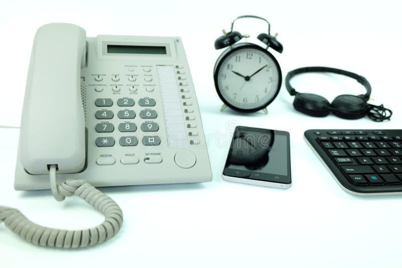 Weißes Büroüberlandleitung Telefon und Smartphone, Tastaturcomputer und Tischuhr benutzten moderne elektronische Geräte lizenzfreie stockfotografie