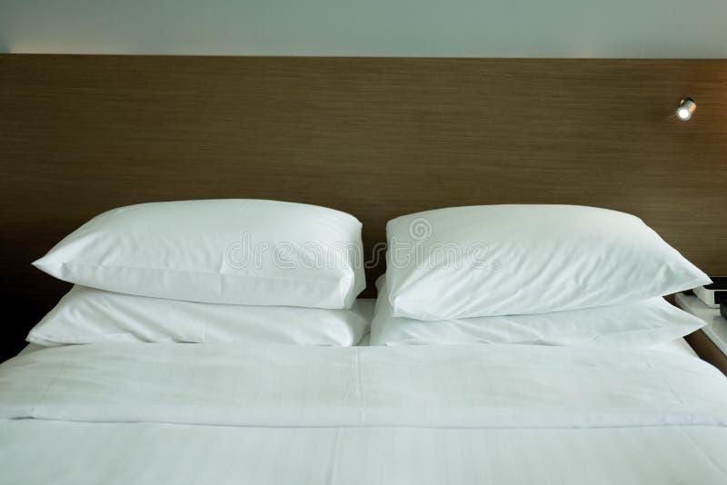 Weißes Bett und weiße Kissen stockbilder