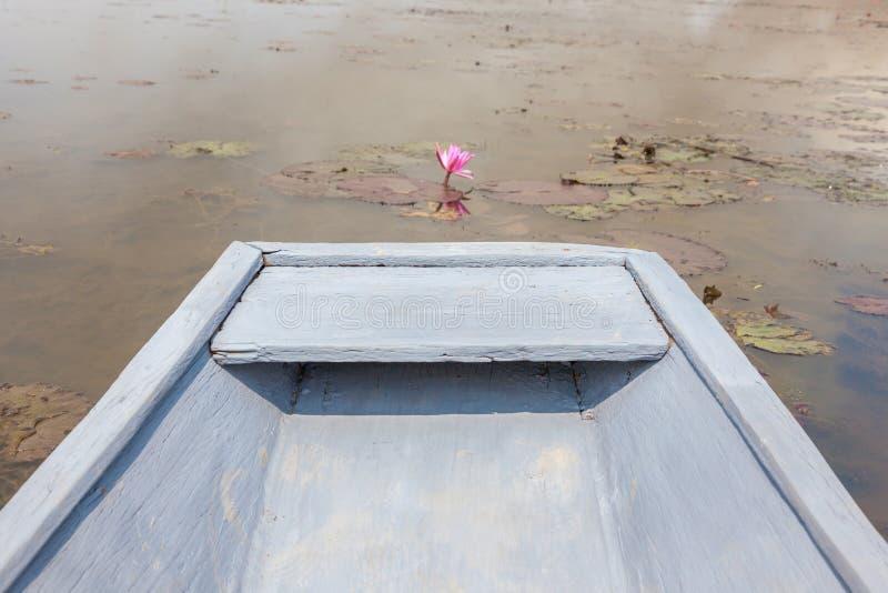 Weißes Boot im rosa Lotosseeroseteich, ruhige ländliche Szene lizenzfreie stockbilder