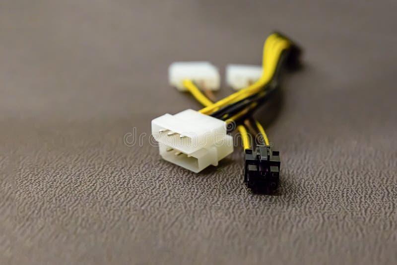 Weißes braunes Schwarzes der Computerdrahtstromkabel-Videokarte auf einem braunen Hintergrundindustriedesign stockfotos