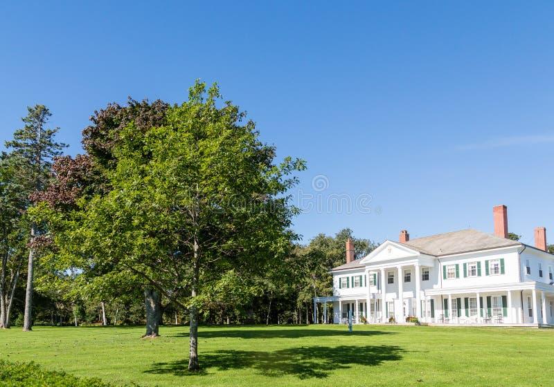 Weißes Columned Haus auf grünem Rasen in Kanada lizenzfreie stockbilder