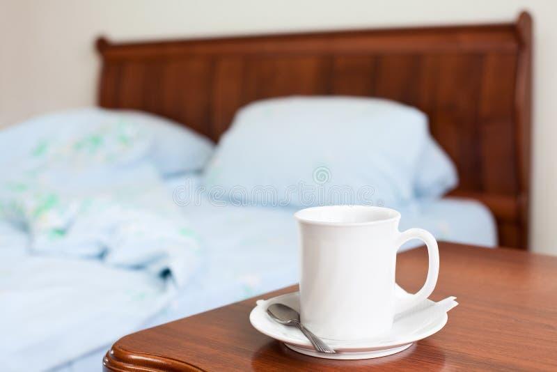 Weißes Cup auf einem Nachttisch lizenzfreies stockbild