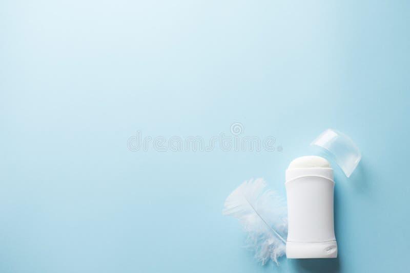 Weißes desodorierendes Mittel oder Antitranspirationsmittel mit Feder auf blauem Hintergrund für Körperhautpflegekonzept Kopieren lizenzfreie stockfotos