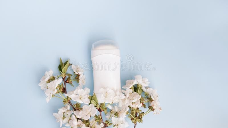 Weißes desodorierendes Mittel und Blumen auf blauem Hintergrund Flache Lagezusammensetzung mit Kopienraum stockfotos