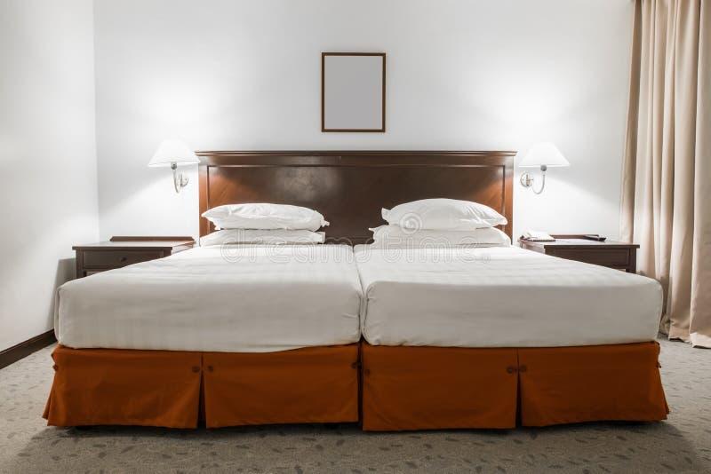 Weißes Doppelbett mit Bilderrahmen im Hotelzimmer stockfoto