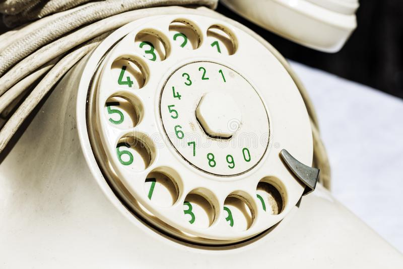 Weißes europäisches Drehskalatelefon mit grünen Zahlen auf dem Fingerrad Altes Weinlesedrehskalatelefon, Nahaufnahmefragment lizenzfreies stockbild