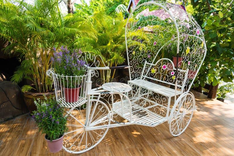 Weißes Fahrrad Garten der Weinlese mit Blume stockfotografie