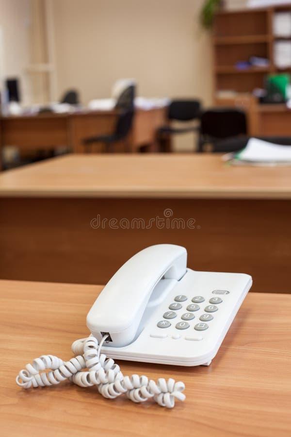 Weißes Festnetztelefon steht auf Schreibtisch, leerer Raum stockbilder