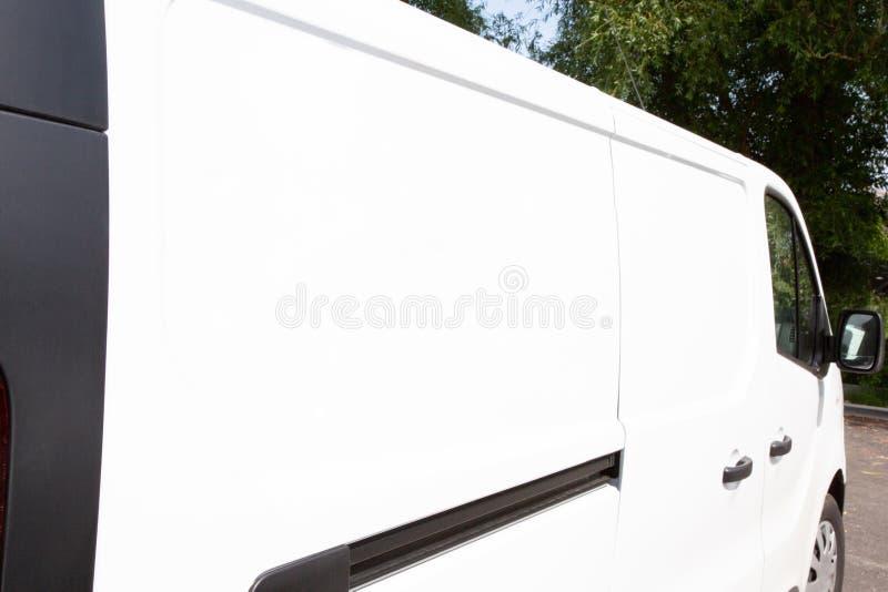 Weißes Frachtmehrzweckfahrzeug Lieferwagens für die Darstellungsebene weiß und leer auf der Seite, zum Ihres eigenen Einbrennens  stockfotografie