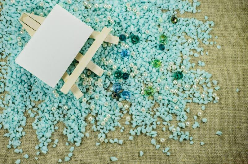 Weißes Gestell mit Papier für Aufschriften auf Kies mit Perle und blauen Perlen stockbilder