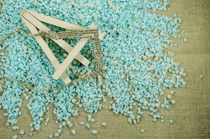 Weißes Gestell mit Perlenperlen und glänzender Halskette lizenzfreie stockfotografie