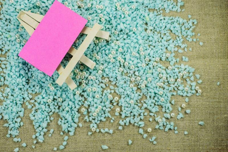 Weißes Gestell mit rosa Papier für Aufschriften auf dem zerfallenen blauen Kies stockfoto