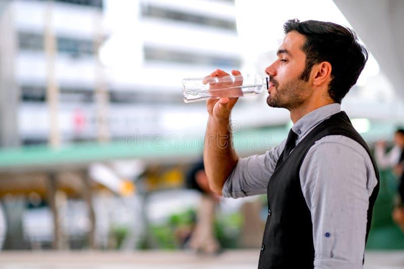 Weißes Getränkwasser des Geschäftsgut aussehenden mannes von der Flasche während der Tageszeit in der Stadt für Erfrischung stockfotografie
