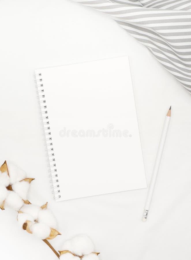 Weißes gewundenes Notizbuch des freien Raumes mit Bleistift, Baumwollblumen und grauem Streifengewebe auf weißen Bettlaken lizenzfreie stockfotos