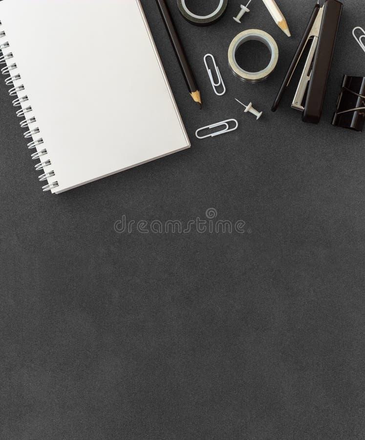 Weißes gewundenes Papiernotizbuch mit Hefter, Papierbüschel, Büroklammern, Stoßstiften und farbigen Bleistiften auf dunklem H stockbild