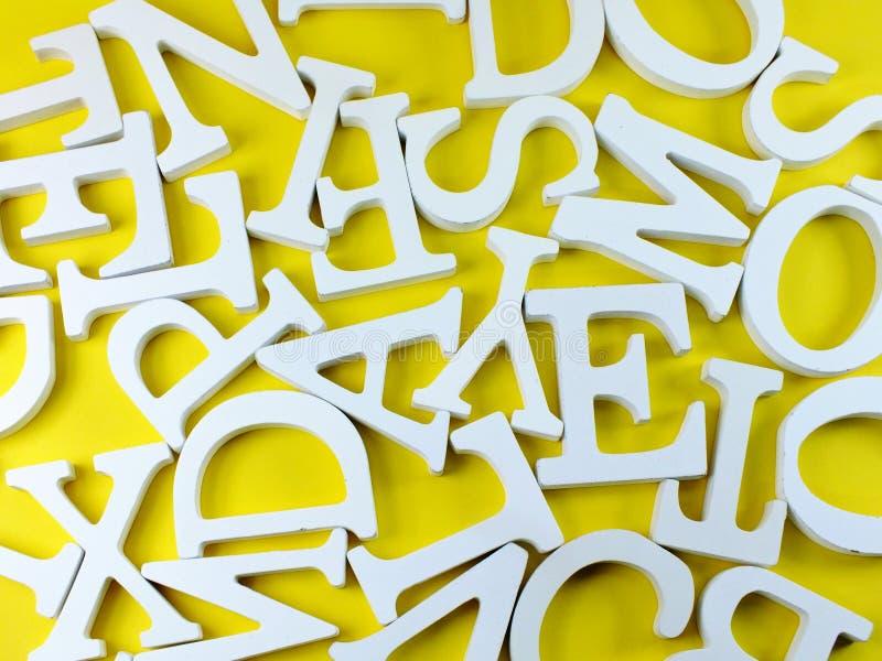 Weißes hölzernes Alphabet beschriftet Draufsicht über gelben Hintergrund stockbild