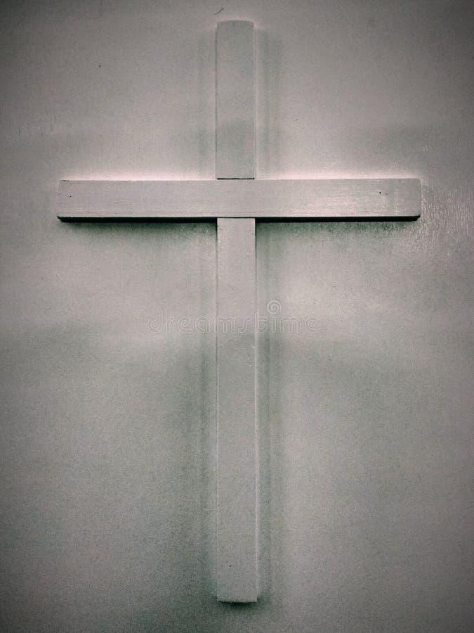 Weißes hölzernes christliches Kreuz des Fotos, das auf einem Hintergrund des grauen Weiß für Gebrauch in den religiösen Symbolen  stockfotografie