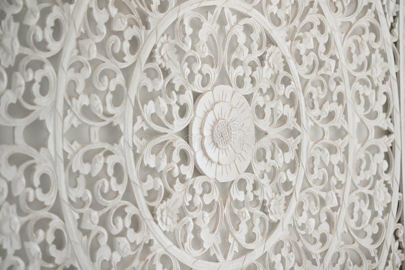 Weißes hölzernes geschnitztes Wandgemälde auf einer Wand lizenzfreie stockfotos