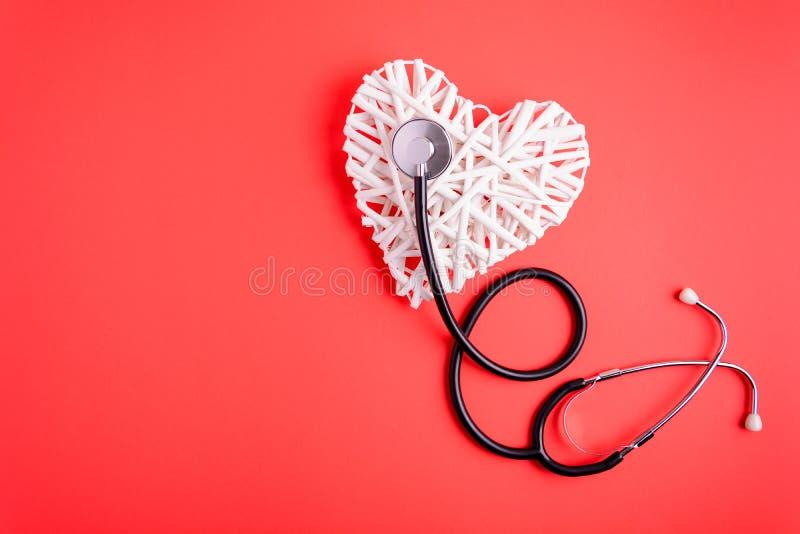 Weißes hölzernes Herz mit schwarzem Stethoskop auf rotem Papierhintergrund Herzgesundheitskonzept lizenzfreie stockbilder