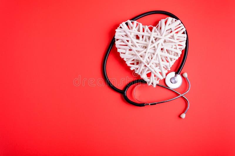 Weißes hölzernes Herz mit schwarzem Stethoskop auf rotem Papierhintergrund Herzgesundheitskonzept stockfotografie
