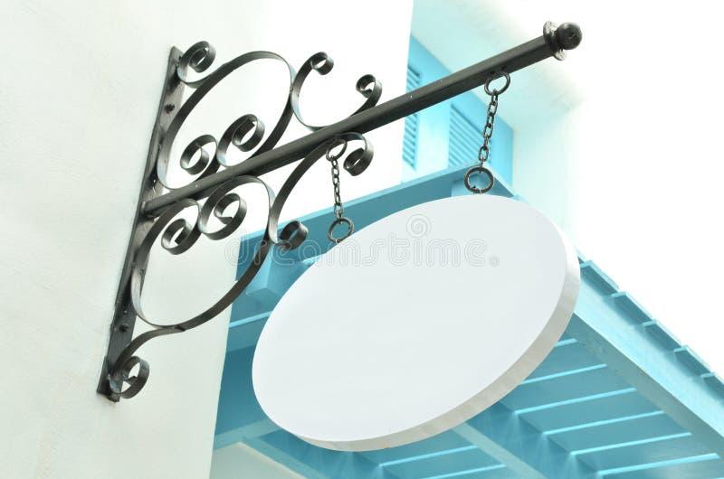 Weißes hölzernes unbelegtes Systemzeichen, das an der Wand hängt lizenzfreies stockfoto