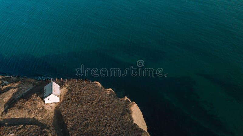 Weißes Haus auf einem Berg über einer Klippe, über dem blauen Meer stockfotos