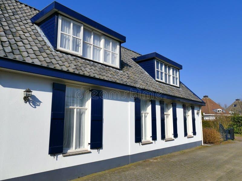 Weißes Haus der Weinlese mit offenem blauem Fenster schließt, Spitzengardine Fensterläden lizenzfreie stockfotografie