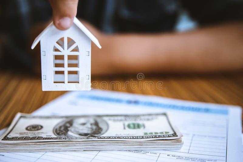 Weißes Haus des Handholding-Modells auf Dollarbanknote Versicherung und Immobilienkonzept der Eigentums-Investition lizenzfreies stockbild