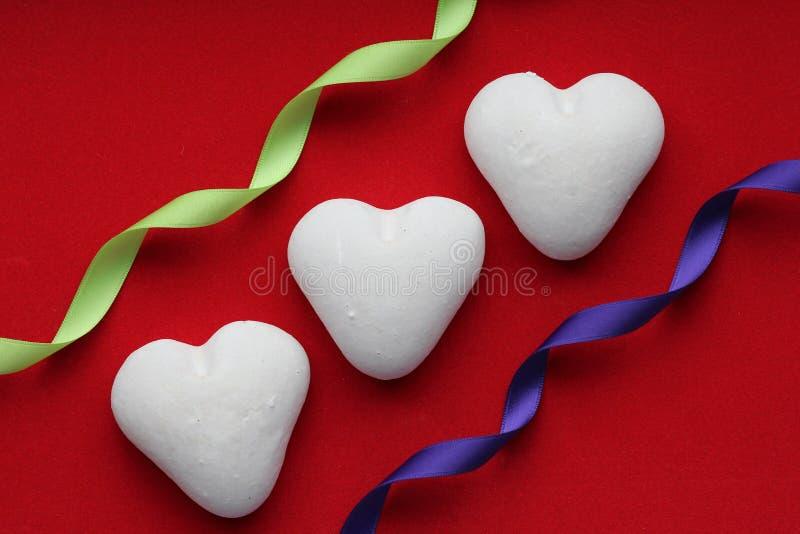 Weißes Herz auf einem farbigen Hintergrund zu Ehren des Valentinstags lizenzfreies stockfoto