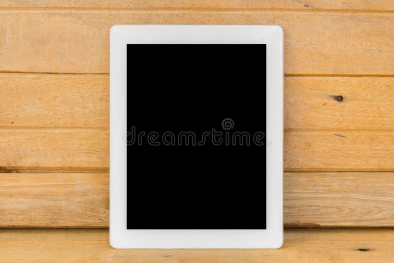 Weißes ipad auf braunem hölzernem Tabellenhintergrund lizenzfreie stockfotos