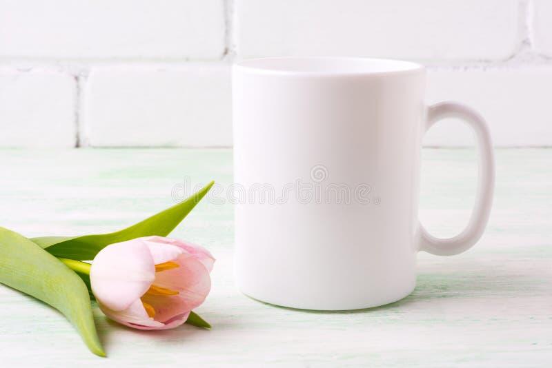 Weißes Kaffeetassemodell mit rosa Tulpe stockfoto
