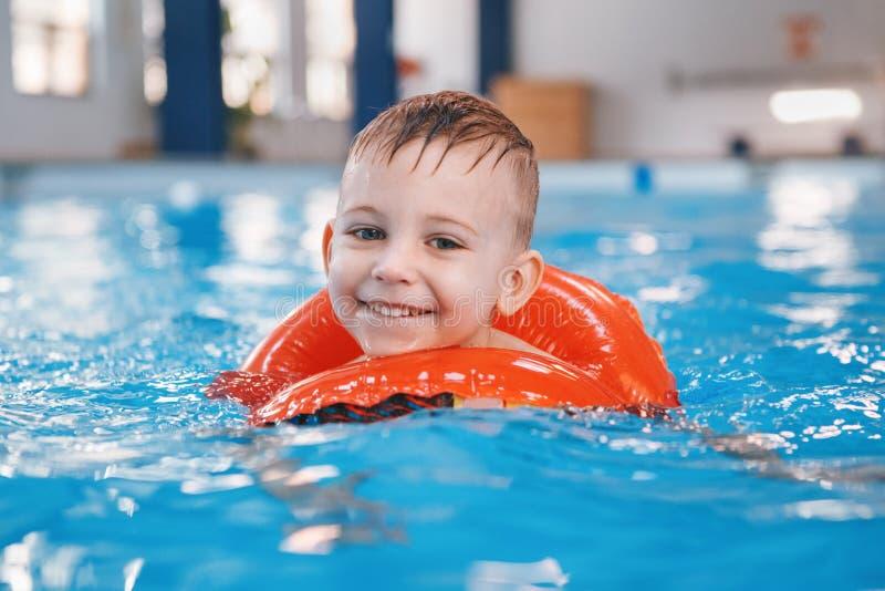 Weißes kaukasisches Kind im Swimmingpool Vorschuljungentraining, zum mit rotem Kreisring im Wasser zu schwimmen stockfoto