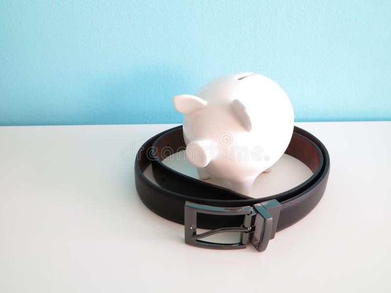 Weißes keramisches Sparschwein mit schwarzem Ledergürtel lizenzfreies stockfoto