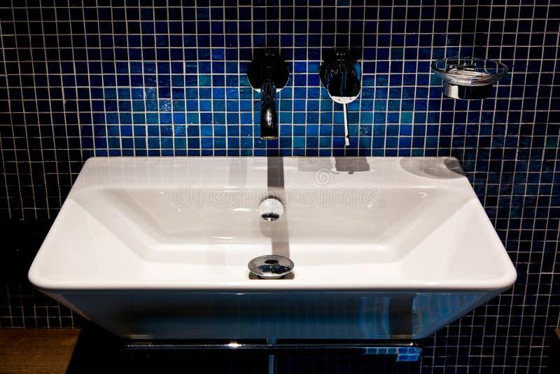 Weißes keramisches Waschbecken mit einem Eisenhahn lizenzfreies stockfoto