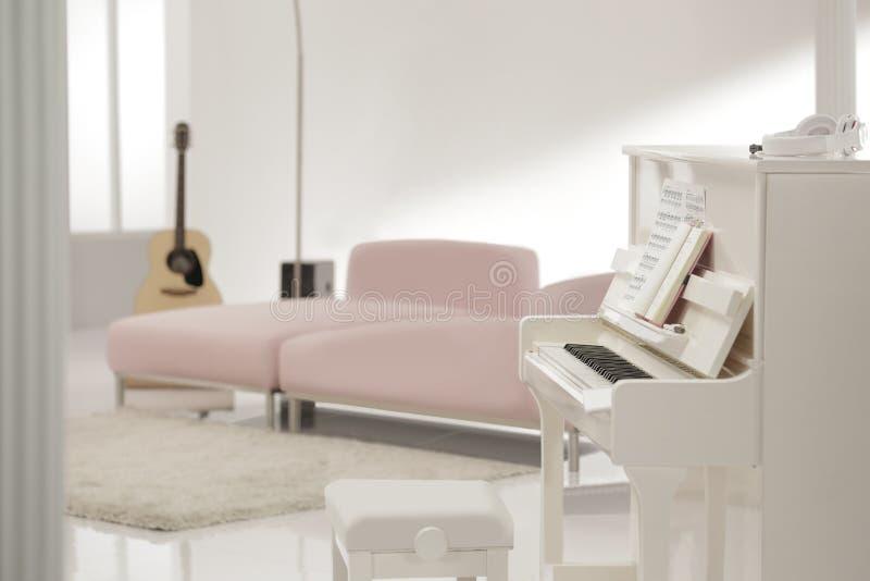 Weißes Klavier im weißen Aufenthaltsraum stockfotografie