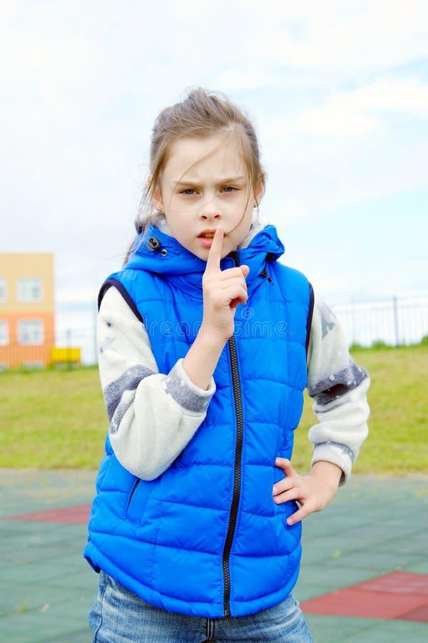 Weißes kleines Mädchen, welches die blaue ärmellose Jacke tut Zeichen Ruhe trägt stockfotografie