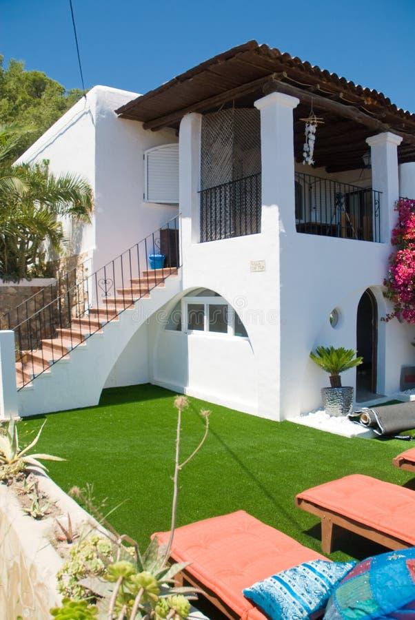 Weißes Landhaus mit Grün und Betten lizenzfreies stockbild