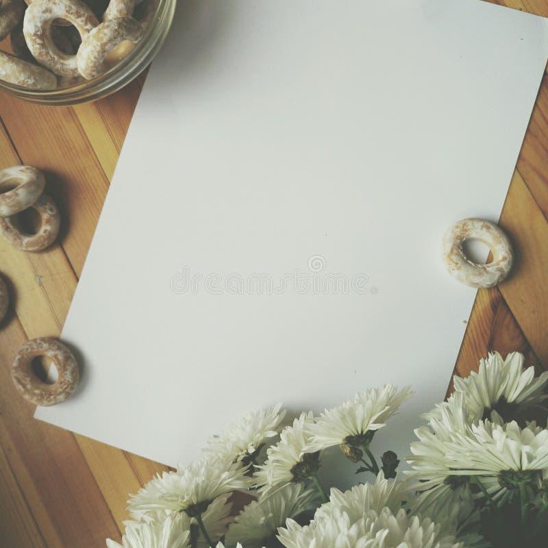 Weißes leeres Blatt Papier für das Schreiben, die weißen Blumen und barel auf Holztisch stockfoto