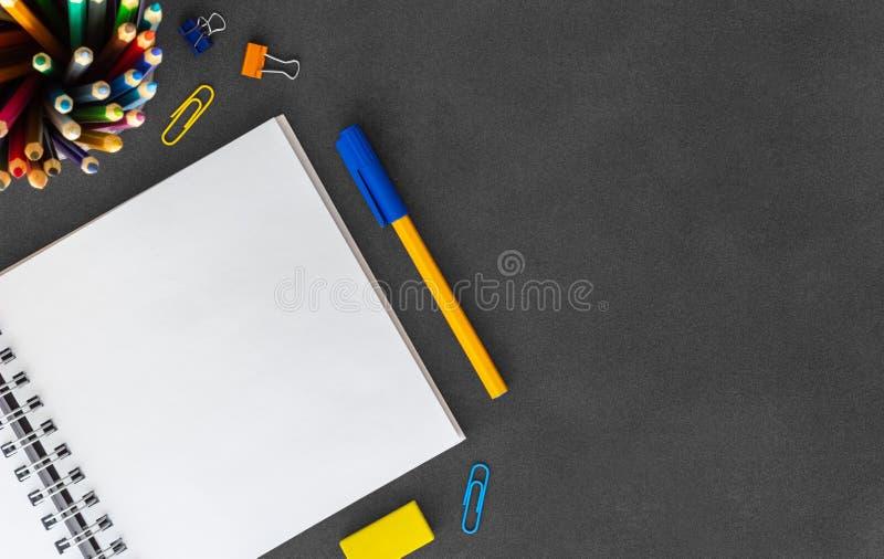 Weißes leeres gewundenes Papiernotizbuch mit Stift, farbige Bleistifte, Radiergummi, Papierbüschel, Büroklammern auf leerem du lizenzfreie stockfotos