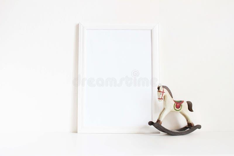 Weißes leeres Holzrahmenmodell mit altem hölzernem Pferdespielzeug auf der weißen Tabelle Angeredete weibliche Fotografie auf Lag stockbild