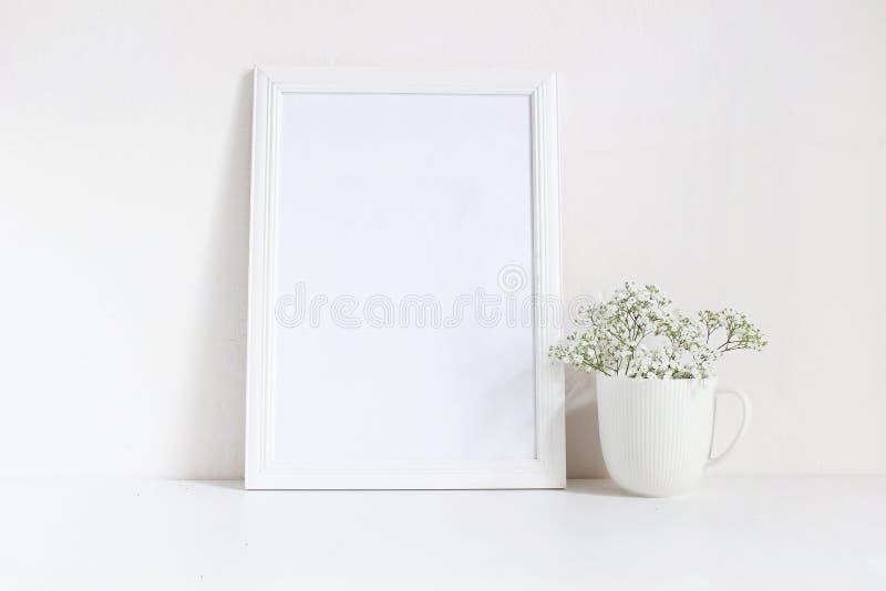 Weißes leeres Holzrahmenmodell mit Babyatem, Gypsophila blüht im Porzellanbecher auf dem Tisch Plakatprodukt lizenzfreies stockfoto
