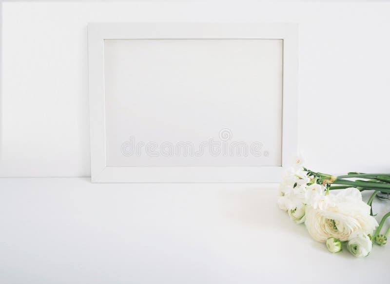 Weißes leeres Holzrahmenmodell mit der persischen Butterblume und der Narzisse blüht das Lügen auf der weißen Tabelle PlakatKonze lizenzfreies stockbild