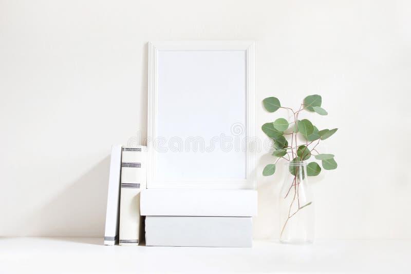Weißes leeres Holzrahmenmodell mit einem Grüneukalyptus verzweigt sich in Glasflasche und in Stapel von den Büchern, die auf dem  stockfotografie