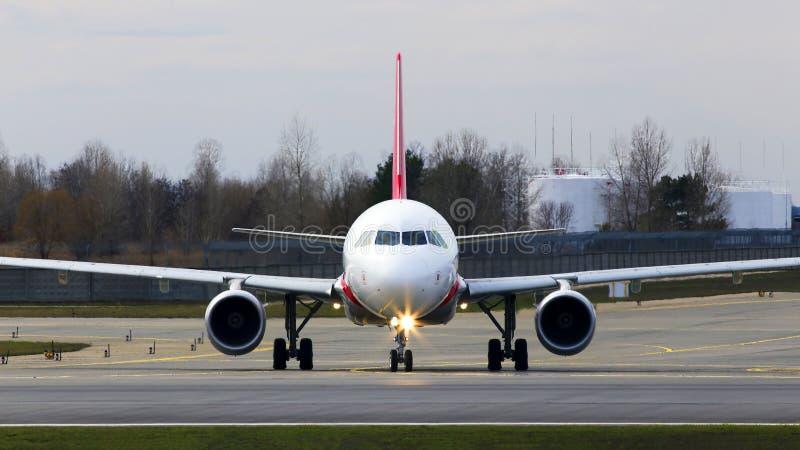 Weißes Luftfahrzeug, das für den Start von der Start-Landebahn des Flughafens vorbereitet ist, frontale Sicht lizenzfreies stockbild