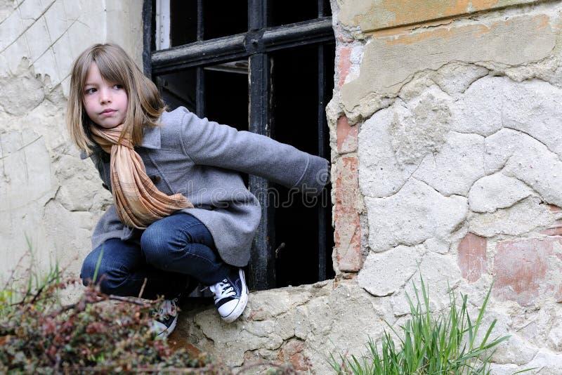 Weißes Mädchen, das auf mittelalterlicher Wand spielt lizenzfreie stockfotos