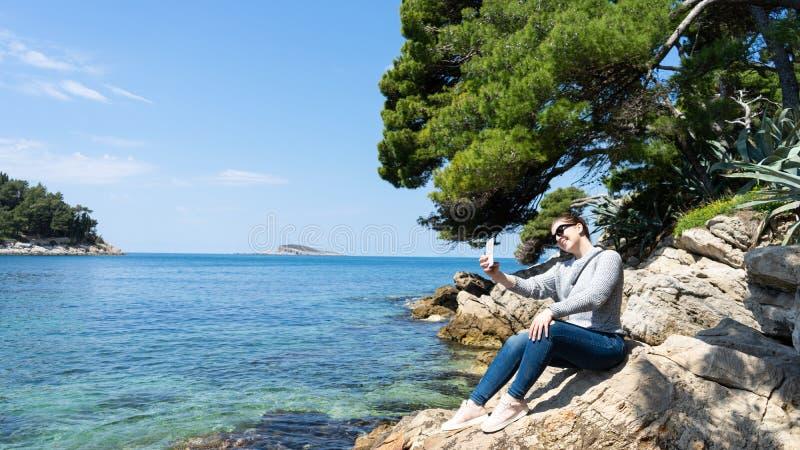 Weißes Mädchen, das ein Foto durch das Meer mit dem intelligenten Telefon machend nimmt selfie am Felsen lächelt Sommerferien am  stockbild