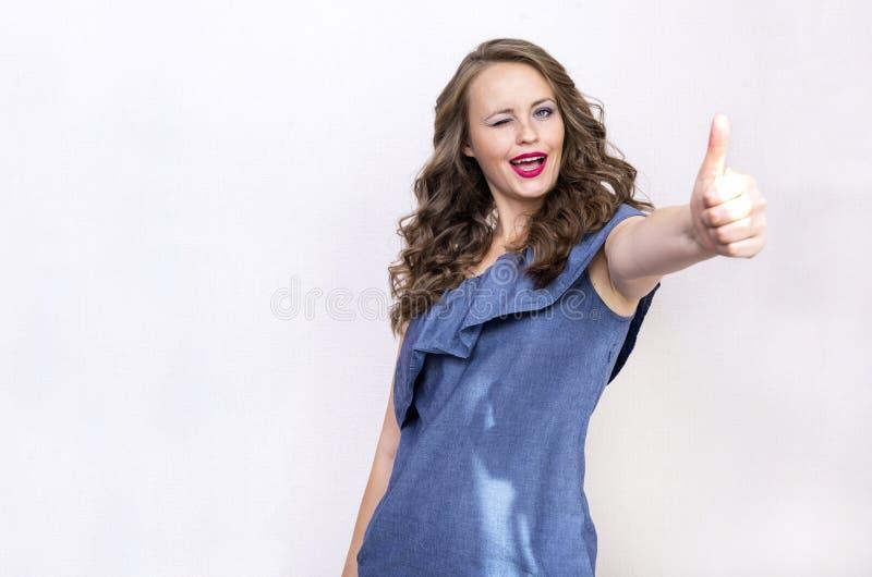 Weißes Mädchen im blauen Kleid mit dem gelockten Haar blinzelt, Lächeln, Showcl lizenzfreie stockbilder